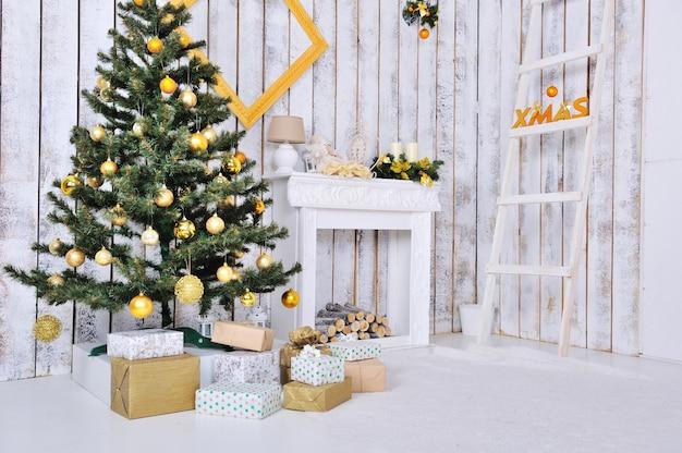 Kerst interieur in witte en gouden kleur met kerstboom en geschenken Premium Foto