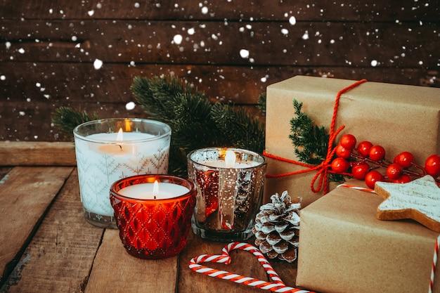 Kerst kaars 's nachts in vrolijk kerstfeest en nieuwjaar vakantie met rustieke handgemaakte cadeau, geschenkdozen. vintage kleurtoon. Premium Foto