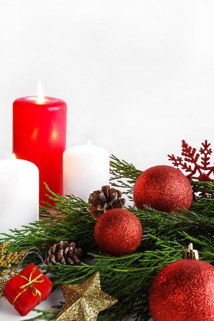 Kerst kaars, vuren pijnboomtakken en kerstversiering ontwerp in een oudejaars st Premium Foto
