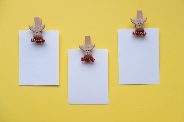 Kerst lege kaarten wasknijpers santa claus op een gele muur met plaats voor tekst Premium Foto