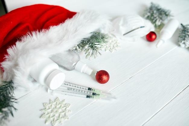 Kerst medisch coronavirus plat leggen, beschermend gezichtsmasker, pillen, antiseptica, decoratie op witte achtergrond, nieuwjaarsthema bovenaanzicht, minimalisme, platte lay-out, covid en gelukkig nieuwjaarsconcept Premium Foto