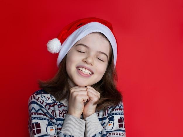 Kerst meisje in kerstmuts maakt wensen voor het nieuwe jaar en kerst kerstdromen Premium Foto