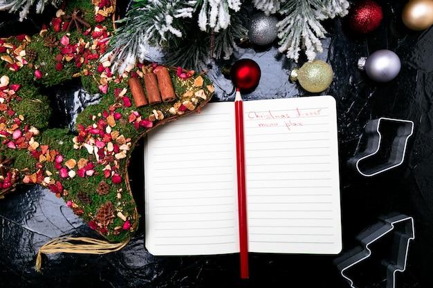 Kerst menu plan. achtergrond voor het schrijven van het kerstmenu. bovenaanzicht notitieboekje met decoratie. Premium Foto