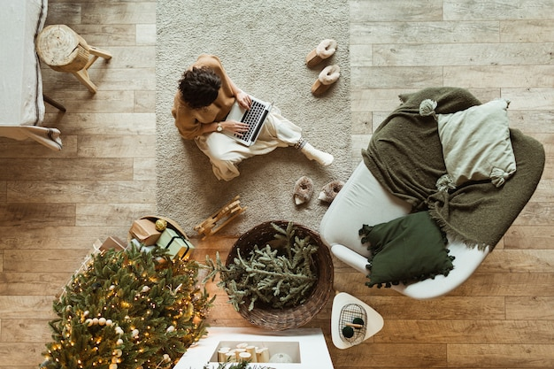 Kerst / nieuwjaar versierde huis woonkamer. mooie vrouw die op laptop werkt. versierde kerstboom, houten vloer, kussens. gezellig comfortabel interieur. thuiswerken. uitzicht van boven. Premium Foto