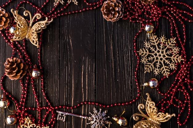 Kerst- of nieuwjaarsframe. kersttakken, dennenappels en rode ketting op houten planken Gratis Foto