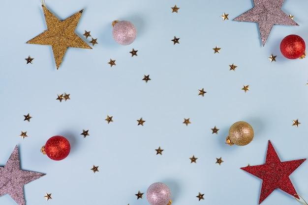 Kerst patroon gemaakt van gouden, zilveren en rode sterren ballen op blauw Premium Foto