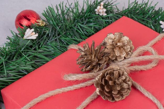 Kerst pinecone speelgoed met rode doos op grijze ondergrond Gratis Foto