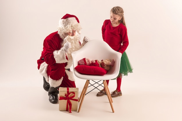 Kerst portret van schattig klein pasgeboren babymeisje en mooie tiener zus gekleed in kerst kleding en man met santa kostuum en hoed Gratis Foto