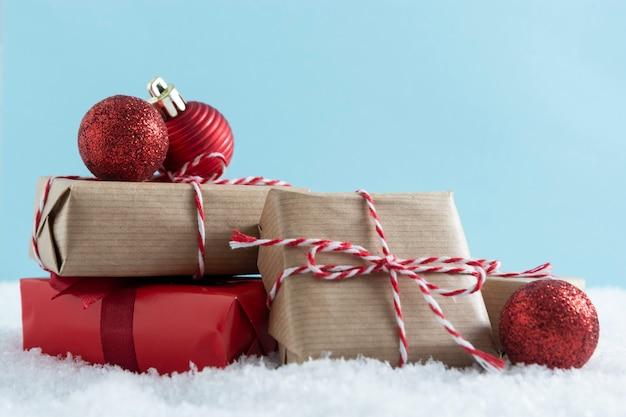 Kerst rode en ambachtelijke geschenkdozen met rode kerstballen op sneeuw. Premium Foto