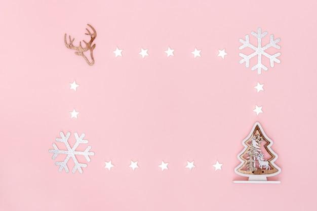 Kerst samenstelling. frame van witte sterren, sneeuwvlokken, chritsmas boom en symbool van herten op pastel roze papieren achtergrond. bovenaanzicht, plat lag, kopie ruimte. Premium Foto