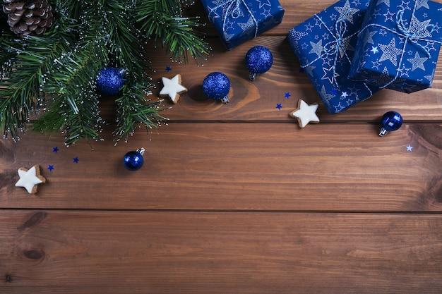 Kerst samenstelling. geschenken, fir tree takken, blauwe decoraties op houten. kerstmis, winter, nieuwjaar vakantie concept. plat leggen, bovenaanzicht, kopie ruimte Premium Foto
