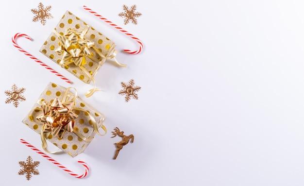 Kerst samenstelling. gouden de giftdozen van kerstmis, suikergoedriet en gouden decoratie op wit. bovenaanzicht, kopie ruimte Premium Foto