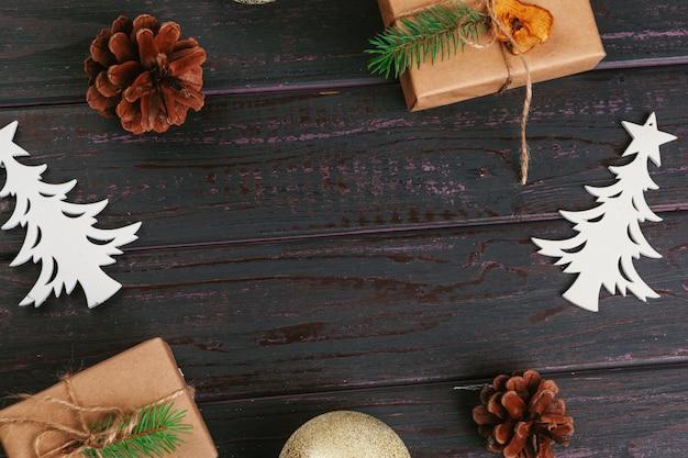 Kerst samenstelling. kerstcadeau, gebreide deken, dennenappels, dennentakken op houten tafel achtergrond. Premium Foto