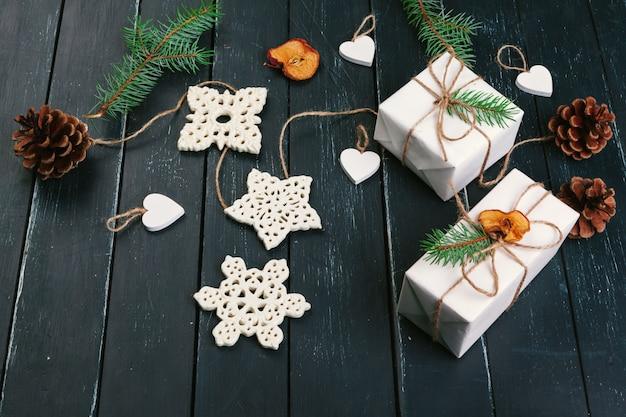 Kerst samenstelling. kerstcadeau, gebreide deken, dennenappels, dennentakken op houten tafel. Premium Foto