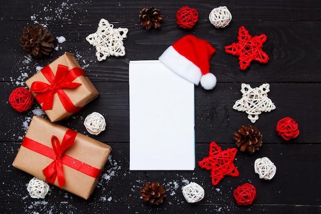 Kerst samenstelling. kerstmisgiften en blocnote met decor op houten zwarte achtergrond. bovenaanzicht, plat lag, kopie ruimte. Premium Foto