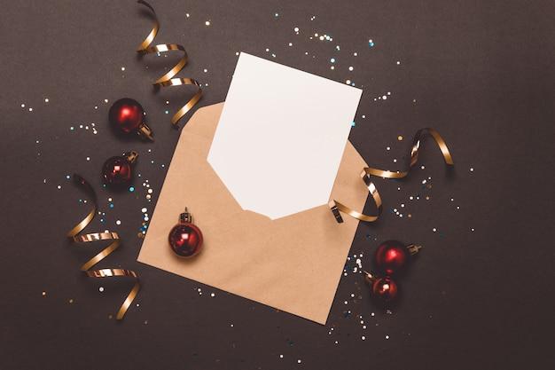 Kerst samenstelling vakantie lege kaart in envelop op zwart. Premium Foto