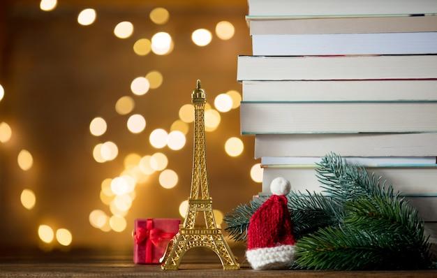 Kerst santa claus hoed met eiffeltoren en stapel boeken Premium Foto