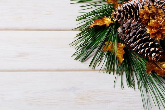 Kerst vakantie achtergrond met gouden versierde sparren en dennenappels Premium Foto