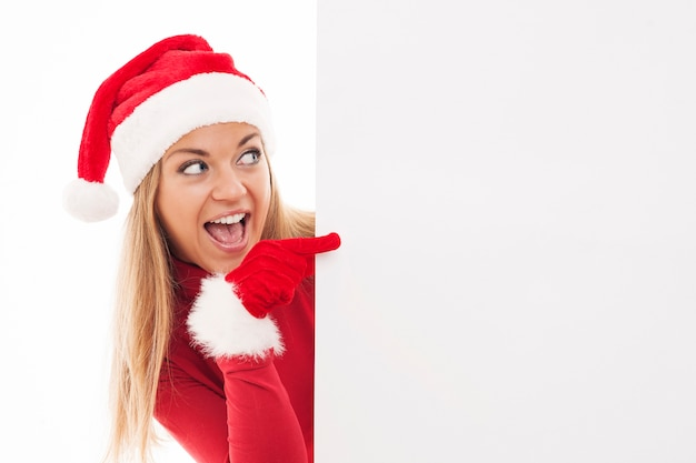 Kerst vrouw wijzend op copyspace Gratis Foto