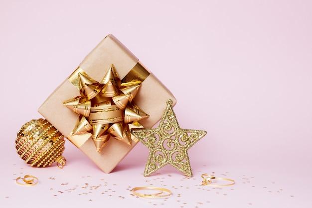 Kerst wenskaart samenstelling. ambachtelijke papieren cadeau met gouden bal, confetti ster en gouden decoratie op roze achtergrond Premium Foto