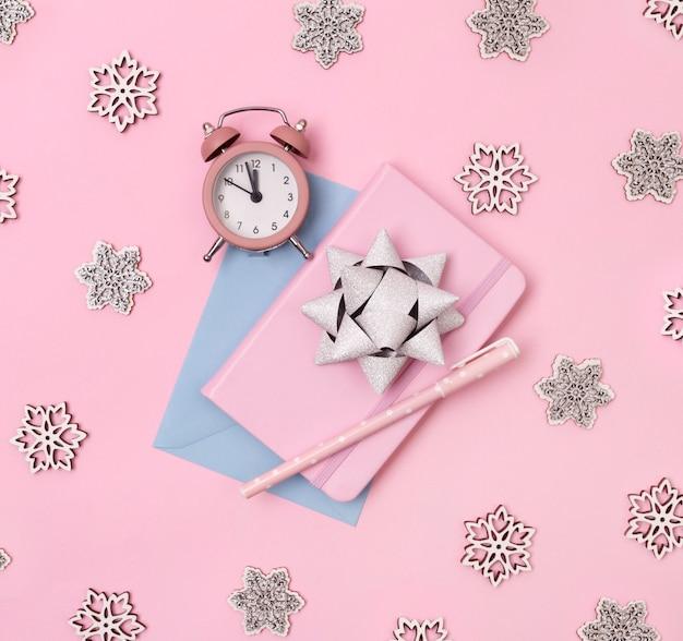 Kerst winter decoraties, zakelijke notitie boek met wekker, sneeuwvlokken en strik op roze achtergrond. Premium Foto