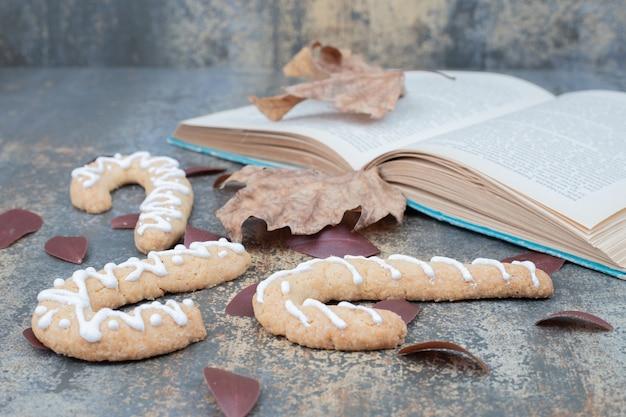 Kerst zoete koekje met blad en boek op marmeren tafel Gratis Foto