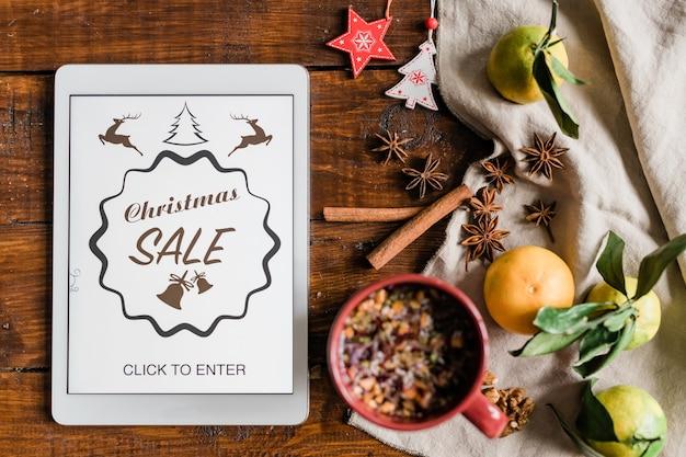 Kerstachtergrond met homepage van online winkel in touchpad, drank, clementines, steranijs, kaneel en decoraties Premium Foto