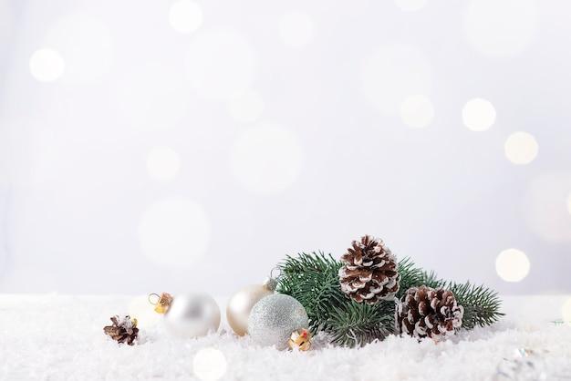 Kerstbal op een fir tak met dennenappel en glitter achtergrond Premium Foto