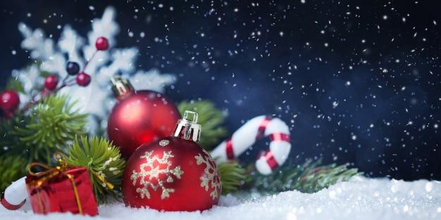 Kerstballen met boom en decoraties op sneeuw Premium Foto