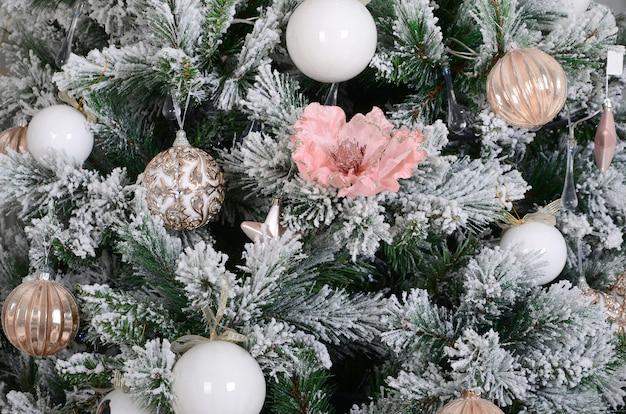 Kerstboom close-up versieren. decoratiebol, sneeuwgroene dennenboom, roze kerstspeelgoed en verlichting Premium Foto