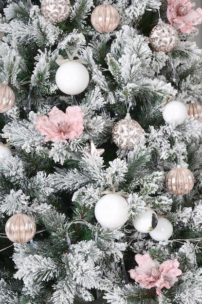 Kerstboom close-up versieren. decoratiebol, sneeuwgroene dennenboom, roze kerstspeelgoed en verlichting. Premium Foto