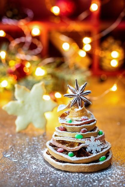 Kerstboom gemaakt van gedroogde stukjes sinaasappel en anijs ster, met feestelijke licht en cookie Premium Foto
