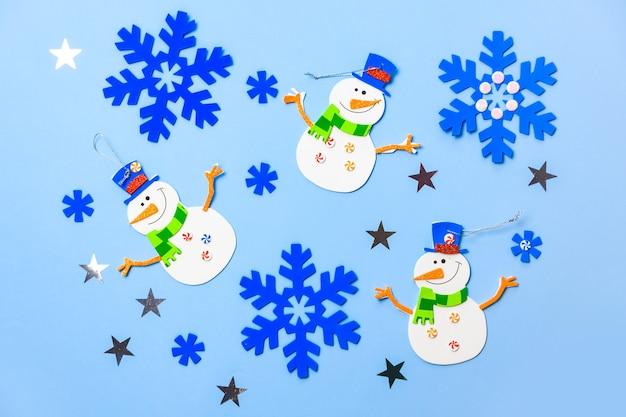 Kerstboom hangende ornamenten. sneeuwman delen op blauwe achtergrond. Premium Foto