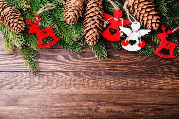 Kerstboom met decoratie en dennenappel op oude houten frame achtergrond Premium Foto