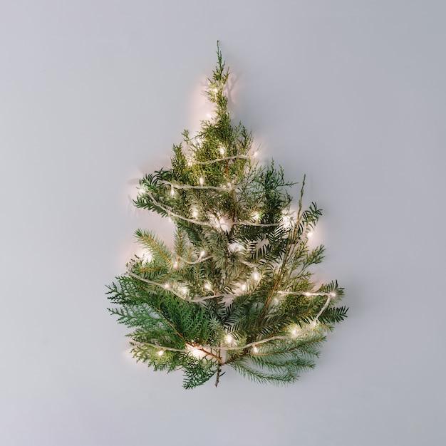 Kerstboom met lampjes op pastel grijs tafelblad. Premium Foto