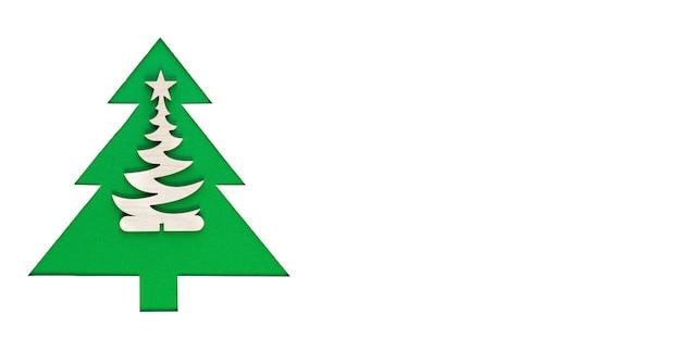 Kerstboom uit papier gesneden op een witte muur. silhouet van groene kerstboom. kerstboom papier snijden ontwerp kaart. papierkunst met kopie ruimte. Premium Foto