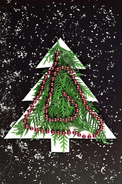 Kerstboom uit papier gesneden op een zwarte muur. silhouet van een kerstboom met groene fir takken. papierkunst met kopie ruimte. Premium Foto