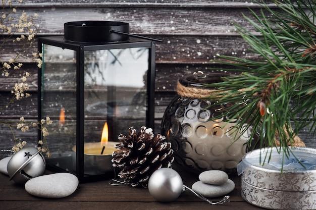 Kerstboom, verlichte kaars en zilveren decor in scandinavische stijl Premium Foto
