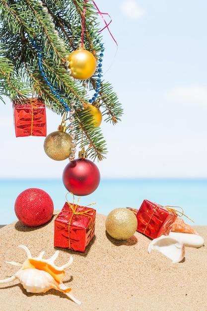 Kerstboomdecoratie op het strand in tropisch. nieuwjaarsvakantie in warme landen Premium Foto