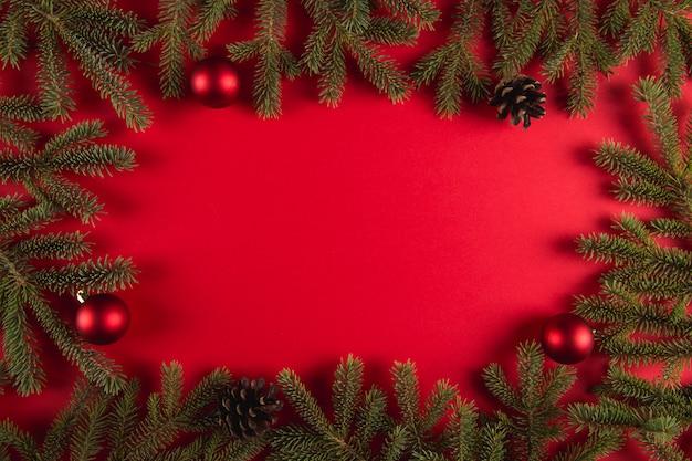 Kerstboomtakken en denneappels op een rood, kerstmis, groetkaart copyspace. Premium Foto