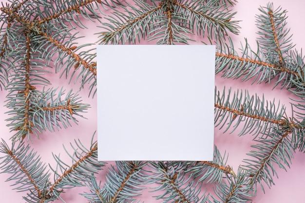 Kerstboomtakken, op roze met copyspace, op grijs, bovenaanzicht Premium Foto