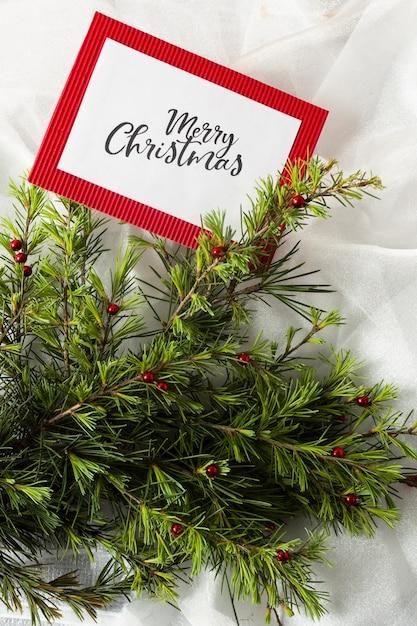 Kerstboomtakken op witte doek met kerstkaartmodel Gratis Foto