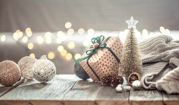 Kerstboomversiering over kerstverlichting bokeh in huis op houten tafel met trui op een muur en decoraties. Gratis Foto