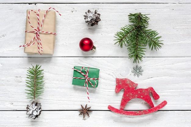 Kerstcadeau, dennenappels, dennentakken, rode bal en speelgoedpaard Premium Foto