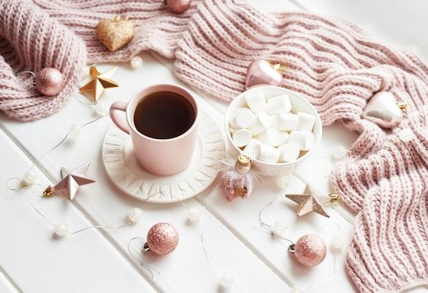 Kerstdecor, ballen, wollen plaid op het raam, huiscomfortconcept, seizoensgebonden wintervieringen. . kerstmis roze kop met marshmallow. Premium Foto