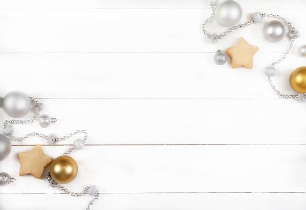 Kerstdecoratie gemaakt van zilveren ballen, kralen, kegels en koekjes op een witte houten ondergrond Premium Foto
