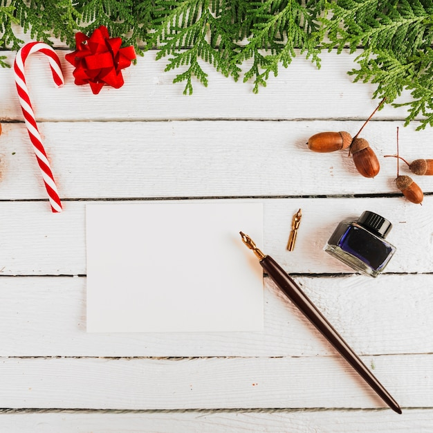 Kerstdecoratie in de buurt van papier en pen Gratis Foto