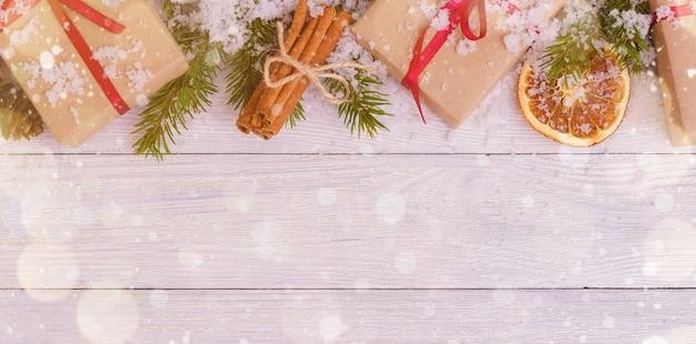 Kerstdecoratie met cadeautjes, sneeuw, sinaasappel en kaneelstokjes Premium Foto