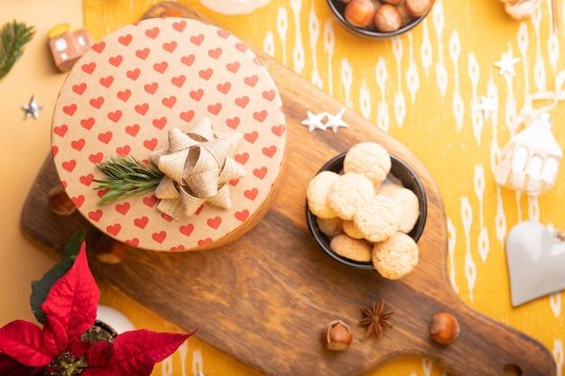 Kerstdecoratie op tafel. flatlay met geschenkdoos, kerstster, noten, kerstversieringen Premium Foto