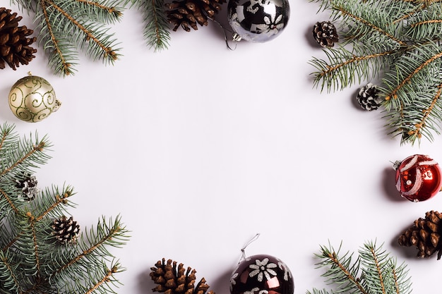 Kerstdecoratie samenstelling dennenappels ballen vuren takken op witte feestelijke tafel Gratis Foto